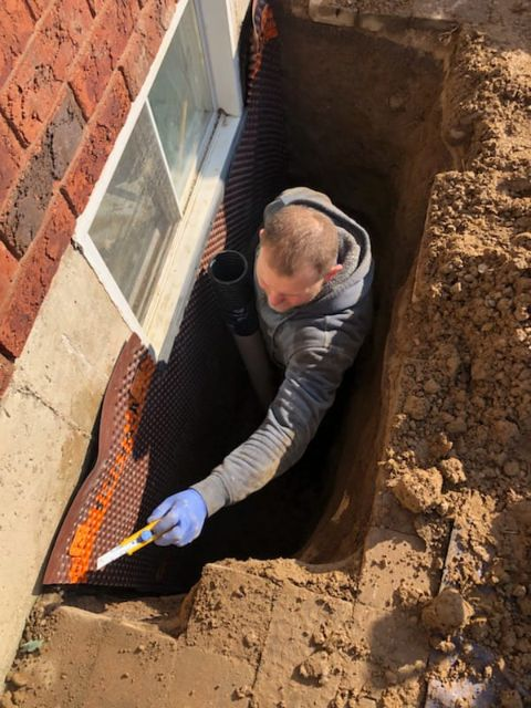 man in excavated hole installing a window well drain