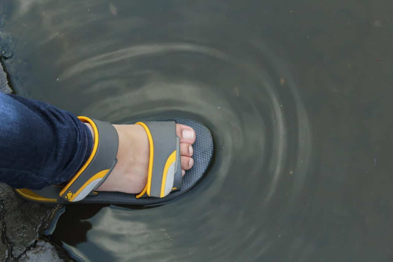man stepping into flooded water