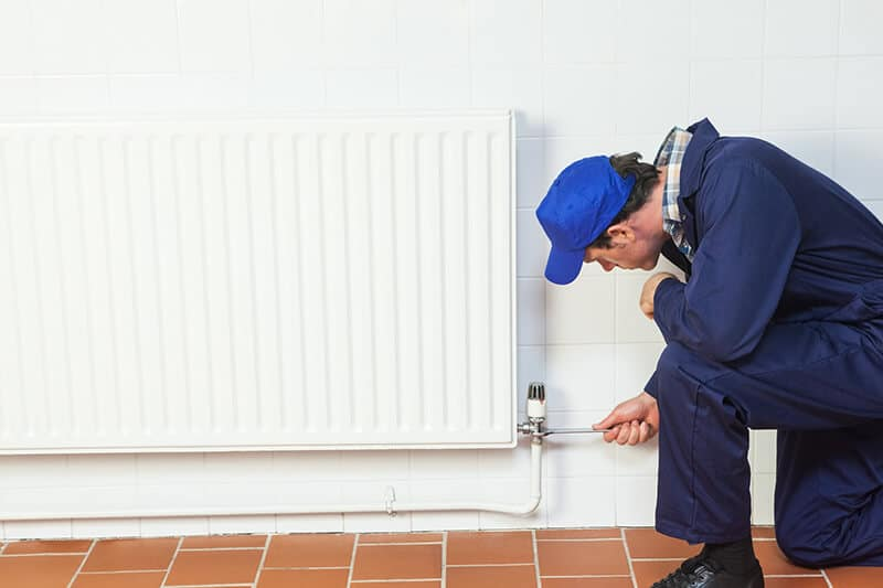 plumber installing radiator into tiled wall